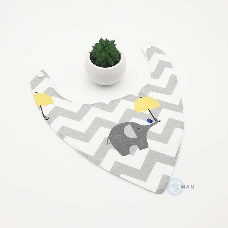 Bavoir bandana pour bébé gris, blanc et jaune avec un petit éléphant tenant un parapluie jaune.