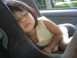 Siège auto avec petite fille qui dort dedans