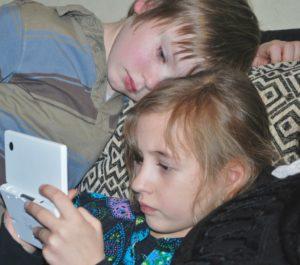 Un garçon et une fille jouent avec une console portable Nintendo