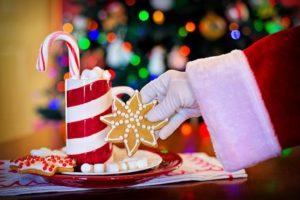 Père Noël prend un biscuit dans une soucoupe posée devant le sapin de Noël