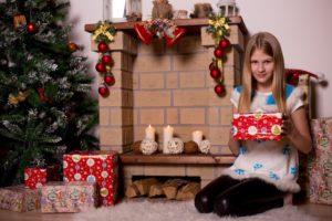 petite fille découvre ses cadeaux devant le sapin de Noël