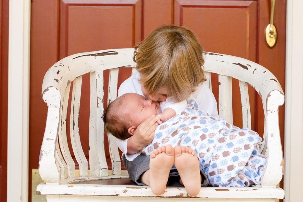 aîné embrasse son petit frère - bébé