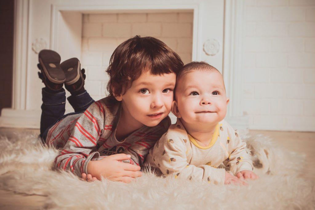 Grand frère à plat ventre avec son petit frère - second bébé