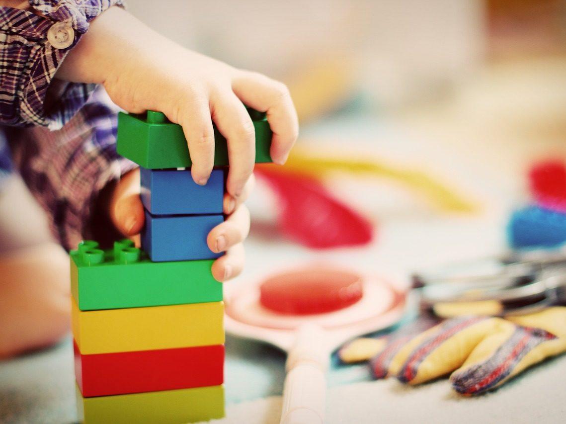 brique en plastique de type LEGO avec main d'enfant