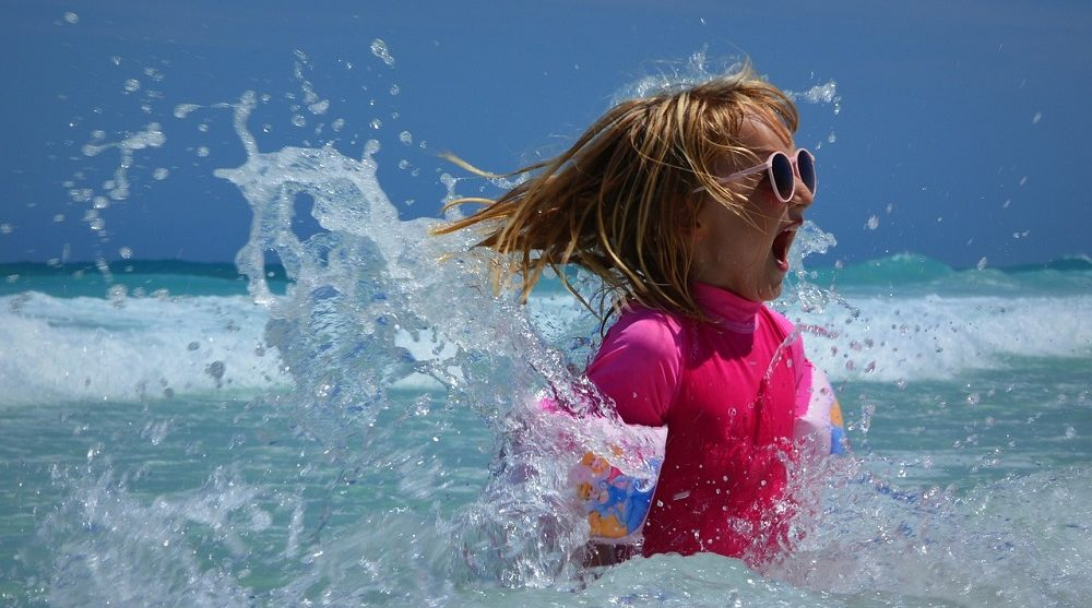 petite fille jouant dans les vagues à la mer
