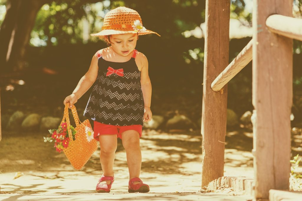 bébé fille marchant avec un sac à la main