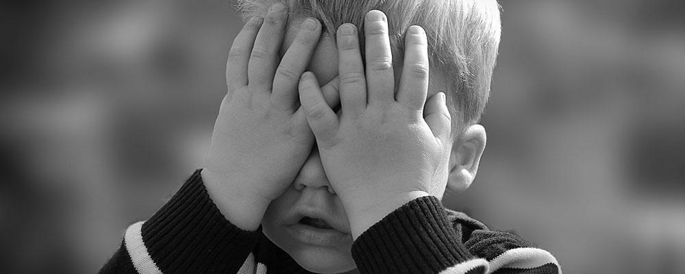 Enfant qui se cache derrière ses mains - encoprésie