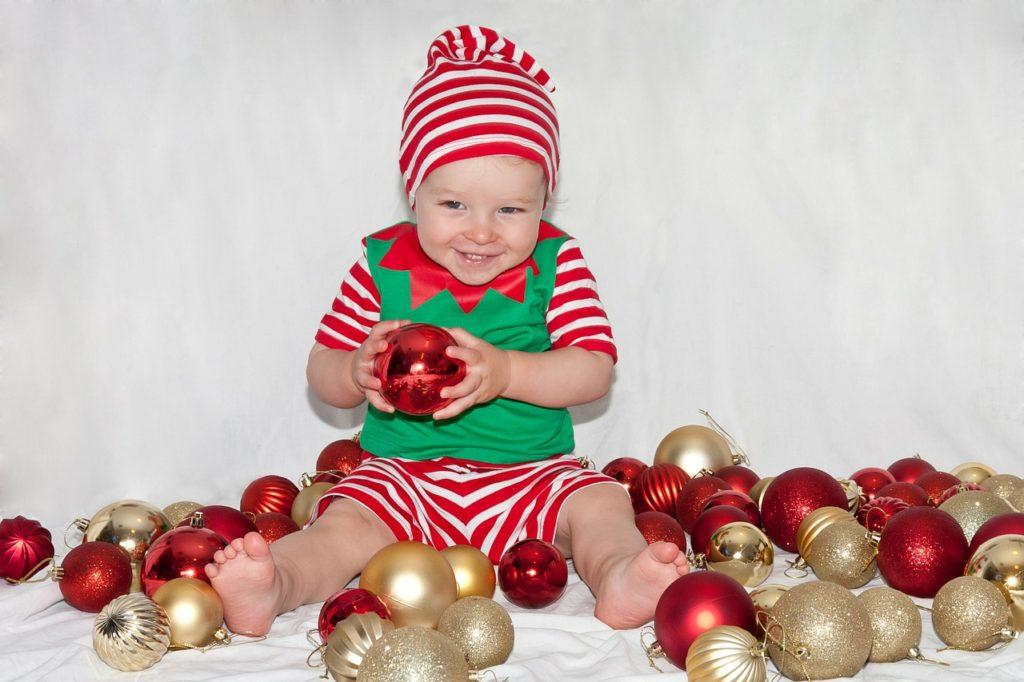 bébé au milieu des boules de noël