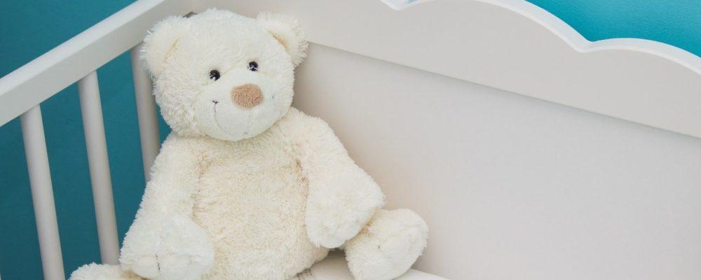nounours en peluche dans un lit de bébé