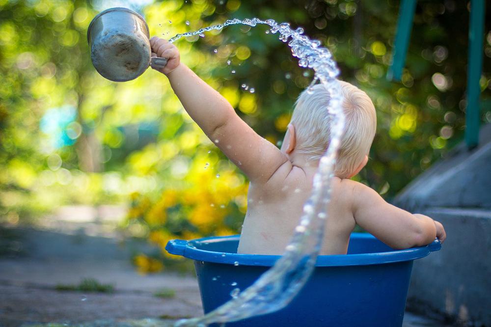 bébé dans le bain qui joue à l'eau