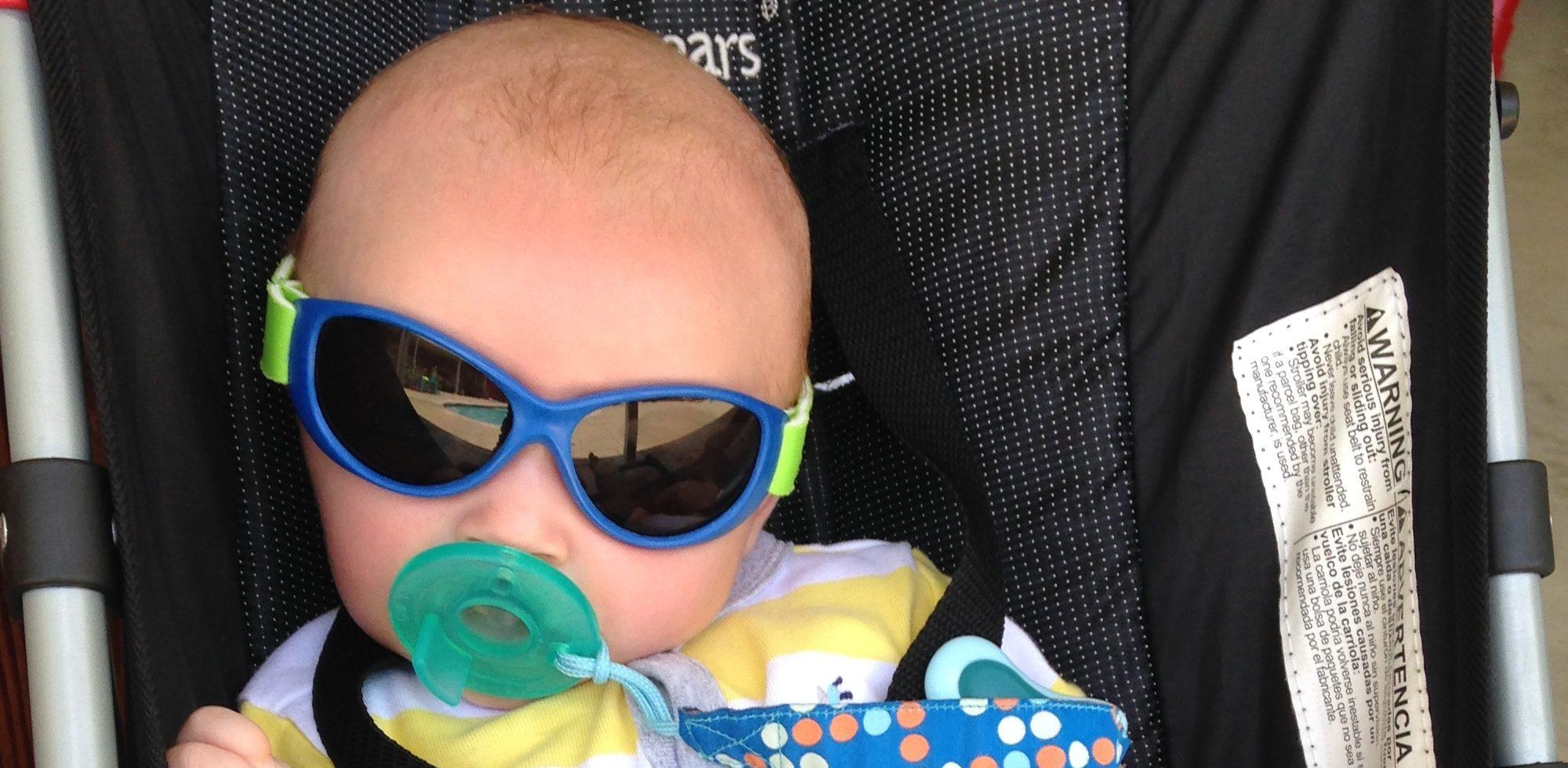 bébé en poussette avec des lunettes de soleil
