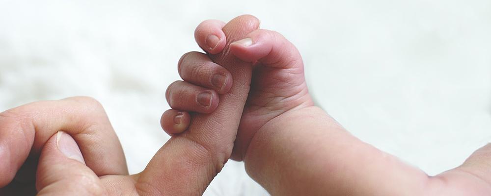 bébé serrant le doigt de papa - bronchiolite