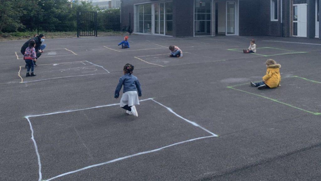 Enfants jouant dans des carrés dans leurs cours pendant le coronavirus