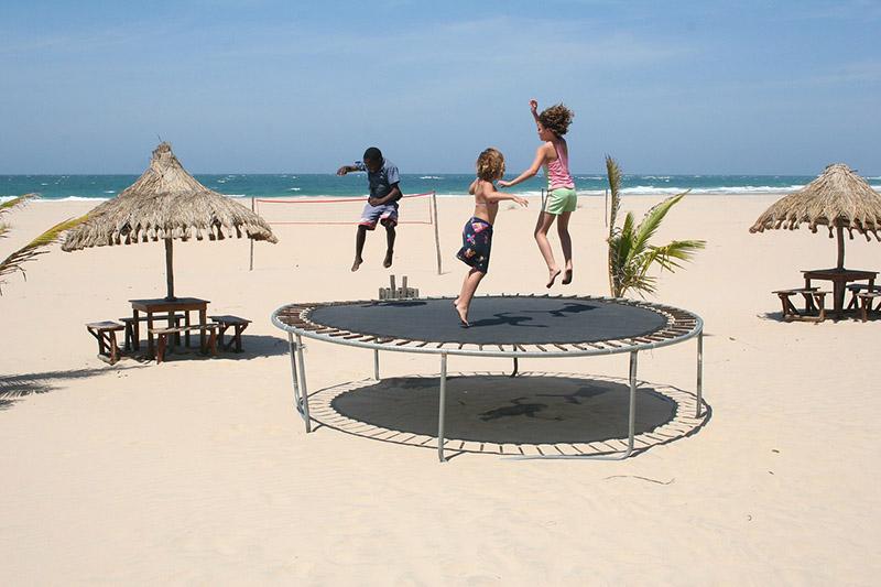 enfant jouant au trampoline devant la mer